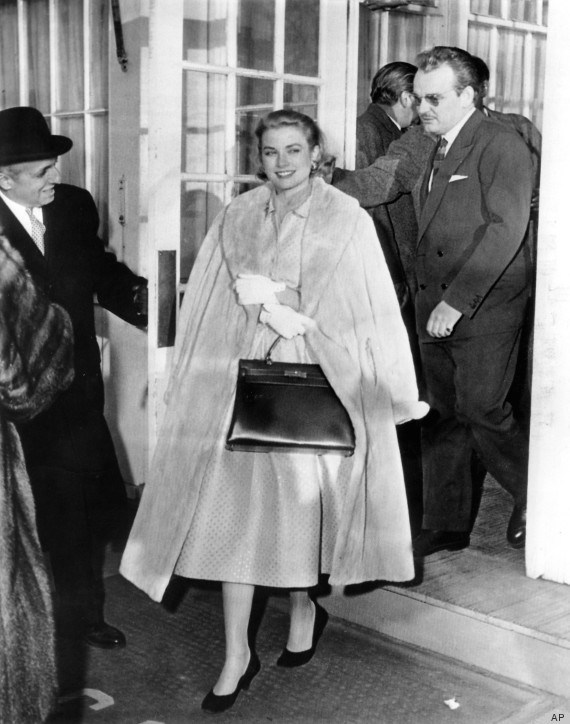 American actress Grace Kelly whose engagement to Prince Rainier of Monaco was announced today, smiles as she leaves the Philadelphia Country Club, on Jan. 5, 1956, after the engagement announcement luncheon, closely followed in the doorway by the 32-year old prince. (AP Photo)